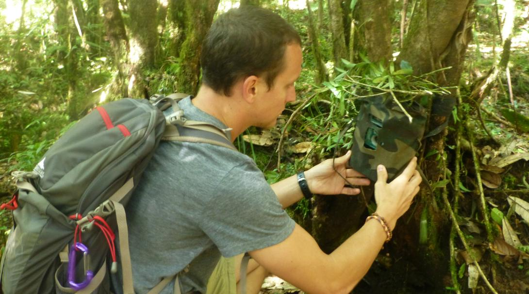 Voluntario ambiental colocando una cámara trampa en los Himalayas, Nepal.